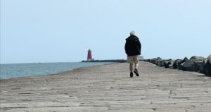 A walker on the South Bull Wall at   Ringsend. Photograph: Brenda Fitzsimons / The Irish Times