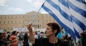 An anti-austerity protester holds a Greek flag during a rally in Athens yesterday. Photograph: John Kolesidis/Reuters