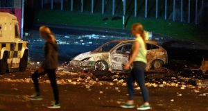 People walk past a burnt out car on the Shore Road in north Belfast on Monday night after  police came under attack from loyalists throwing petrol bombs. Photograph: Reuters