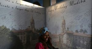 A well-wisher smiles after signing a giant birthday card for Nelson Mandela in Pretoria. Photograph: Siphiwe Sibeko/Reuters