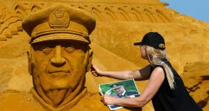 Sand sculptor Irina Sokolova works on a portrait of Belgian King Albert II during the sand sculpture festival in Blankenberge, northern Belgium. Photograph: Reuters/Yves Herman