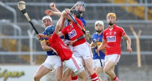 Tipperary's Brian Stapleton and Tomás Hamill tussle with Cork's  Rob O'Shea and Jamie Coughlan at Semple Stadium, Thurles, last night. Photograph: Inpho