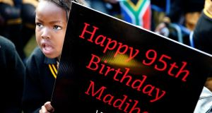 Children hold placards as they gather to wish the former president a happy birthday. Photograph: Mike Hutchings/Reuters