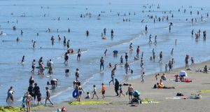 Swimmers and sunbathers on Portmarnock beach enjoy the long-running fine weather. The expectation of a bumper year for water quality could be scuppered by beach-goers – Fingal County Council collected 3,000 bags of rubbish left on beaches last weekend, for example. Photograph: Alan Betson