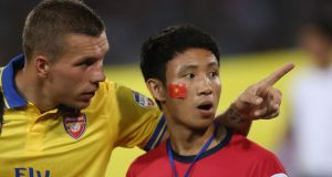 Lukas Podolski of Arsenal talks with fan Vu Xuan Tien (The Running Man) ahead of the international friendly between Vietnam and the visiting Arsenal side. Photograph: Chris McGrath/Getty Images