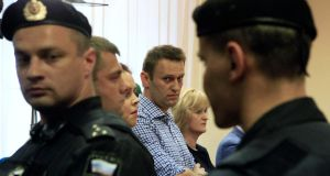Russian protest leader Alexei Navalny (centre) stands yesterday inside a courtroom in Kirov where he was sentenced to five years in jail for theft. Photograph: Reuters/Sergei Karpukhin