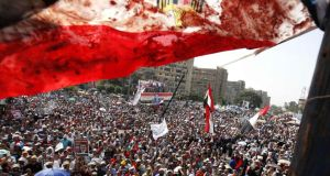 An Egyptian flag stained with blood flutters over members of the Muslim Brotherhood and supporters of deposed Egyptian president Mohamed Morsi as they shout slogans during a protest outside the Raba El-Adwyia mosque in Cairo on July 8th. Photograph: Reuters