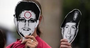 In defence of whistleblowers: protesters in Berlin hold masks of Edward Snowden (left) and Bradley Manning.  Photograph: Thomas Peter/Reuters