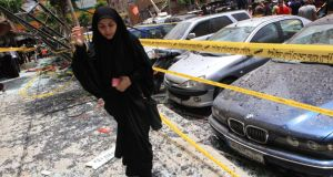 A woman walks over shattered glass, past damaged cars near the site of an explosion last week in Beirut's southern suburbs. Photograph: Khalil Hassan/Reuters