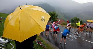 Spectators shelter from rain as a group of riders pass  during the 204.5 km 19th stage of the centenary Tour de France  from Bourg d'Oisans to Le Grand Bornand, in the French Alps. Photograph: Eric Gaillard/Reuters