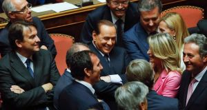 Italy's former prime minister Silvio Berlusconi talks to colleagues during a vote in the Senate in Rome yesterday.