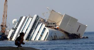 The capsized cruise liner Costa Concordia lying surrounded by cranes outside Giglio harbour. The huge liner struck a rock outside the port of Giglio in January 2012 and keeled over on to its side, setting off a chaotic night-time evacuation of more than 4,000 passengers and crew. Photograph: Giampiero Sposito/Reuters