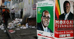 Election campaign posters adjacent to uncollected refuse  in a street in the Zimbabwean capital Harare. Photograph: Reuters/Philimon Bulawayo