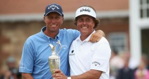 Phil Mickelson  holds the Claret Jug with caddie Jim Mackay after the final round of the 142nd British Open Championship at Muirfield. Photo:  Andrew Redington/Getty Images