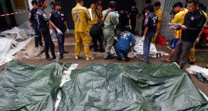 Rescue and forensic personnel work among bodies of victims of a crash, at a hospital in Kanghoi in Thailand. Photograph: Athit Perawongmetha/Reuters