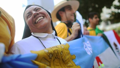 Nun Concepcion Hernandez, originally from Mexico, holds an Argentinian flag while awaiting the arrival of Pope Francis outside the Metropolitan Cathedral in Rio de Janeiro, Brazil. Hernandez is currently a Catholic missionary in Argentina. More than 1.5 million pilgrims are expected to join Pope Francis for his visit to the Catholic Church's World Youth Day celebrations.  Photograph: Mario Tama/Getty Images