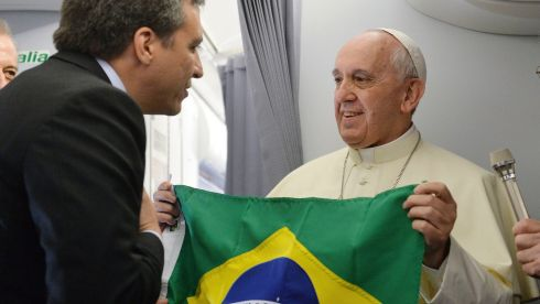 Pope Francis accepts a gift of a Brazilian flag from a journalist travelling on the papal flight to Rio de Janeiro.  Photograph: Ansa/Luca Zennaro/Pool/Reuters
