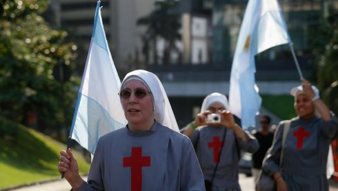Nuns from Argentina walk to greet Pope Francis as he drove through downtown Rio de Janeiro. Photograph: Stefano Rellandini/Reuters