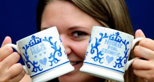 Rachel West holds two commemorative royal baby mugs as they go into production at the Emma Bridgewater Factory in Stoke On Trent, to celebrate the birth of Prince George of Cambridge. Photograph: Rui Vieira/PA Wire