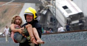 A fireman carries a wounded victim from the wreckage of a train crash near Santiago de Compostela.