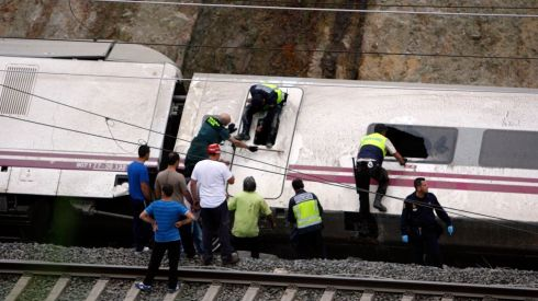 Rescue workers pull victims from the  crash.  A woman who was close to the site of the accident told the radio station that she had first heard a loud explosion and then seen the train derailed.  Photograph: Oscar Corral/Reuters