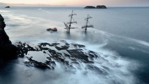 The Astrid early yesterday morning on rocks at Ballymacus point off the mouth of Oysterhaven harbour. Divers are assessing the tall ship to see if salvage is possible. Photograph: Michael Prior