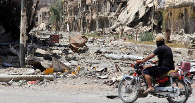 A Free Syrian Army fighter rides a motorbike along a damaged street filled with debris in Deir al-Zor, Syria, yesterday. Photograph: Karam Jamal/Reuters