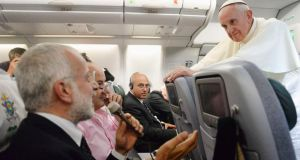 Pope Francis listens to a journalist's question as he flies back to Rome following his visit to Brazil. Photograph: Luca Zennaro/Reuters