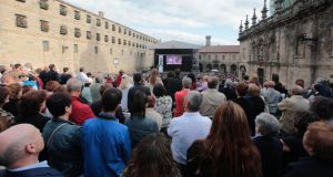People watch a service in memory of the victims of the Santiago train crash on a screen outside the Cathedral of Santiago de Compostela. Photograph: Miguel Vidal/Reuters.