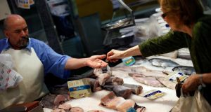A woman pays for her purchase at a fish shop in central Madrid. Rising food and energy prices across the OECD has pushed up inflation, data published today shows. Photograph: Susana Vera/Reuters