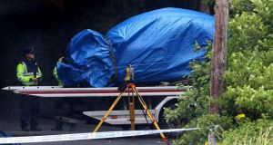 A car is removed from the scene in Westport, Co Mayo, where the bodies of two missing children where found in a crashed car.