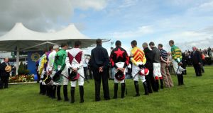 Jockeys stand for a minute's silence yesterday at the Galway Races in deference to the late broadcaster Colm Murray. Photograph: Brenda Fitzsimons