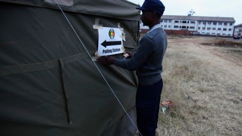 A Zimbabwean policeman attaches a sign  as voting gets underway in Harare. Photograph: Philimon Bulawayo/Reuters