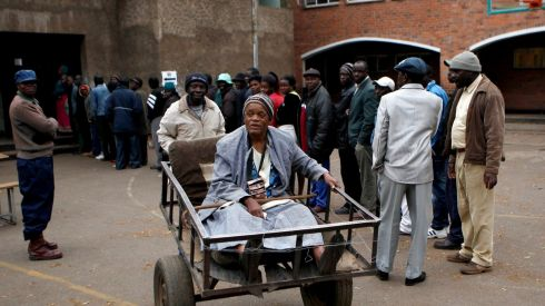 Chizema Majika, 80, is transported on a push cart after casting her vote in Mbare township outside Harare. Photograph: Siphiwe Sibeko/Reuters.