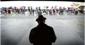 A lone punter takes cover from the rain at the Galway Races. Photograph: Brenda Fitzsimons