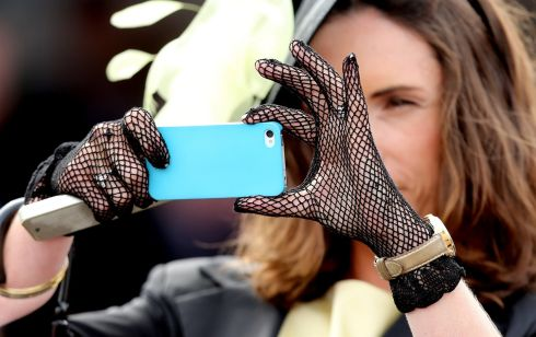 A woman takes pictures at the races. Photograph: Inpho/James Crombie