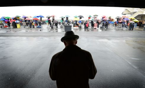 A lone punter takes cover from the rain. Photograph: Brenda Fitzsimons/The Irish Times