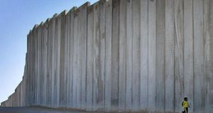 A Palestinian boy runs in front of a concrete wall on the outskirts of Jerusalem. Photograph: Reuters