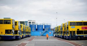 A security guard picutred by parked up buses in Dublin Bus Ringsend Garage in Dublin City. Photograph: Aidan Crawley/The Irish Times.