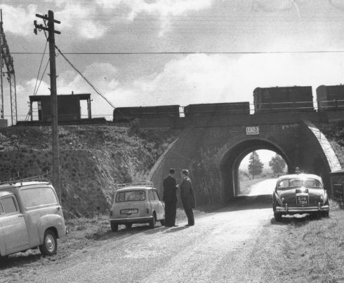 Investigators at the scene of the Great Train Robbery, Sears Crossing in Buckinghamshire, watching a train on the bridge.  (Photo by Evening Standard/Getty Images)
