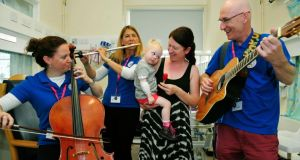 Brenda Clifford from Co Kildare with her daughter, three-year-old Rowan Clifford, who is a patient in Our Lady's Hospital, Crumlin, listening to the National Concert Hall Kids' Classics players Gráinne Hope (cello), Julie Maisel (flute) and Liam Merriman (guitar). Photograph: Aidan Crawley