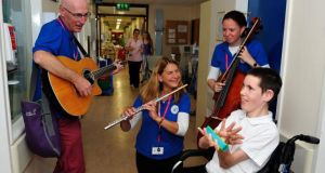 13-year-old Ian Byrne from Bray, Co Wicklow, a patient in Our Lady'sChildrens Hospital, Crumlin, listens to The National Concert Hall Kids' Classics players Gráinne hope (cello) Julie Maisel (flute) and Liam Merriman (guitar). Photograph: Aidan Crawley
