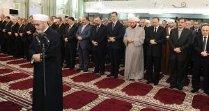 Syria's president Bashar al-Assad (centre) taking part in Eid al-Fitr prayers at Anas bin Malek mosque in Damascus yesterday. Photograph: Reuters/Sana/Handout