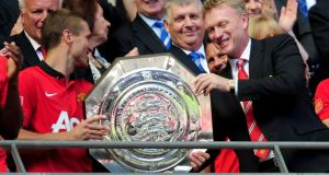 Nemanja Vidic of Manchester United and manager David Moyes with the trophy after victory over Wigan in the FA Community Shield. Photograph: Jamie McDonald/Getty Images