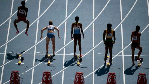 English Gardner of the US jumps in the air before the start of her women's 100 metres heat. Photograph: Dylan Martinez/Reuters