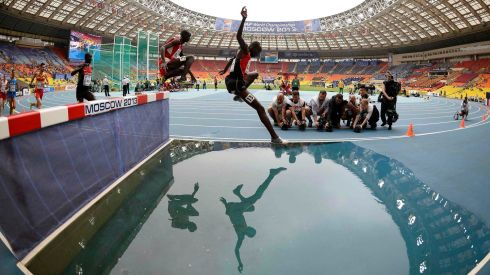 Benjamin Kiplagat (centre) of Uganda jumps a water obstacle in the men's 3000 metres steeplechase. Photograph: Dylan Martinez/Reuters