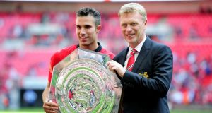 Robin van Persie of Manchester United and manager David Moyes pose with the trophy after victory in the FA Community Shield