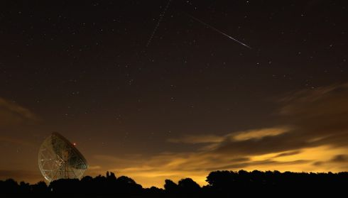 A Perseid meteor streaks across the sky over the Lovell Radio Telescope at Jodrell Bank in Holmes Chapel, UK. The annual display, known as the Perseid shower because the meteors appear to radiate from the constellation Perseus in the northeastern sky, is a result of Earth's orbit passing through debris from the comet Swift-Tuttle.  Photograph: Christopher Furlong/Getty Images