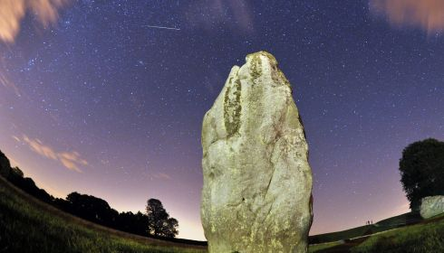 A Perseids meteor flies over a standing stone at the Avebury's Neolithic henge monument in Wiltshire, UK.  Photograph: Tim Ireland/PA Wire