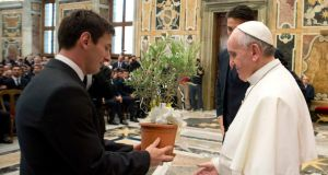 Pope Francis receives a gift from Argentine soccer player Lionel Messi (left) and Italy's goalkeeper Gianluigi Buffon (obscured) during a private audience at the Vatican. Photograph: Osservatore Romano/Reuters
